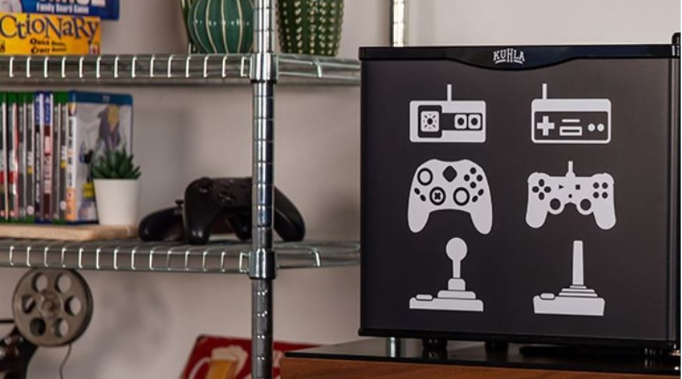 The image shows a small fridge with retro controllers and joysticks printed on it on a shelf in a bedroom.