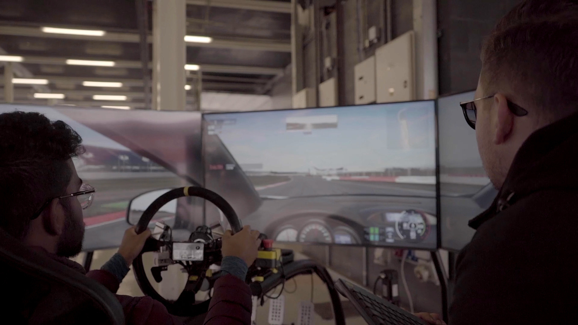 Man sim racing with a supervisor working on handcontrols.