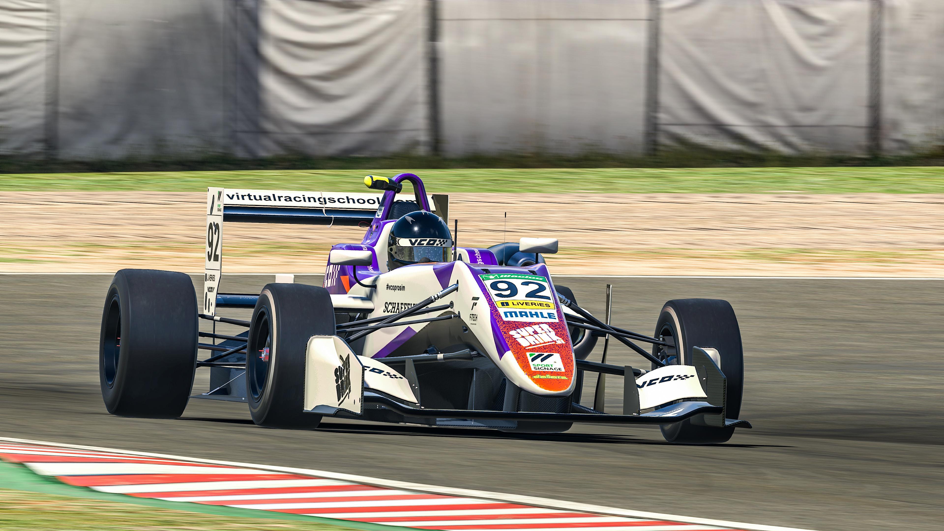 Coanda Simsport liveried Formula Three car driving at speed.